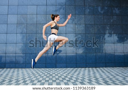 Young woman in sportswear  jumping and running outdoors, urban style. #1139363189