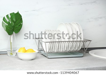 Different clean plates in dish drying rack on kitchen counter #1139404067