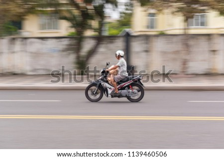 22/07/2018 - Vung Tau city, Vietnam Panning shot of a man who carry a bag of bread on his motorbike #1139460506