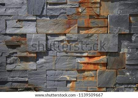Close up outdoor view of part of a stone bricks wall with several rusty shapes. Pattern of grey geometric blocks. Graphic image with various polygons, angles and lines. Abstract architectural picture.