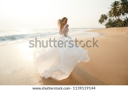 Happy young bride woman in white dress  running, have fun on clean sandy beach waves of azure sea or ocean on sunset, summer vacation at water. Wedding rest, relax honeymoon concept. Royalty-Free Stock Photo #1139519144