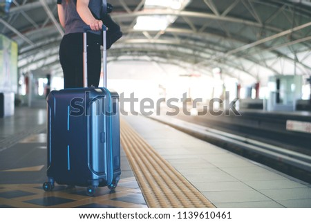 Woman with suitcase waiting for a train in modern station platform #1139610461