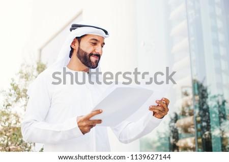 Handsome middle eastern arab businessman holding documents #1139627144