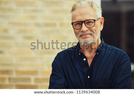 Content senior man with a beard and wearing glasses smiling while standing outside in front of his home #1139634008