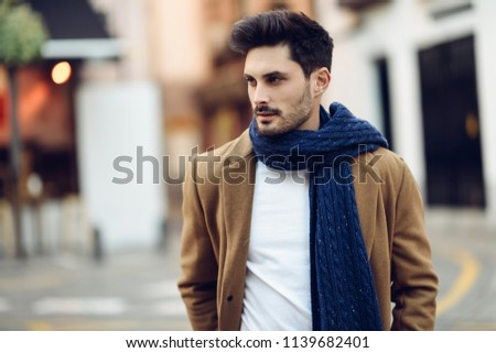 Young man wearing winter clothes in the street. Young bearded guy with modern hairstyle with coat, scarf, blue jeans and t-shirt. #1139682401