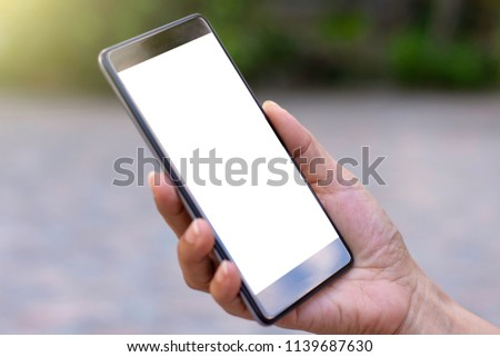 Woman hand holding black mobile smartphone with blank white screen isolated on blurred background.clipping path. #1139687630