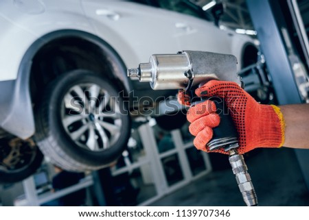 Professional car mechanic working with pneumatic wrench in auto repair service. Repair of wheels #1139707346