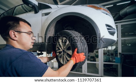 Car mechanic inspecting wheel and suspension detail of lifted automobile at repair service station. Auto service. #1139707361