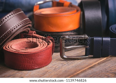 Collection of leather belts on a wooden table Royalty-Free Stock Photo #1139746826
