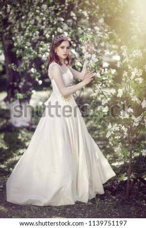 Beautiful young bride in white dress in Apple orchard with white flowers #1139751197