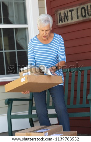 Mature attractive woman with delivered cardboard boxes #1139783552