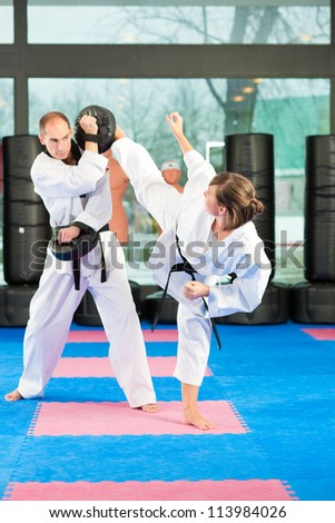 People in a gym in martial arts training exercising Taekwondo, both have a black belt #113984026