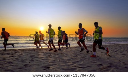 Durres, Albania - circa August, 2017: Football sport team is engaged in jogging training at sea at sunset. Thay make a run along the sea coast. cinematic steadicam shot #1139847050