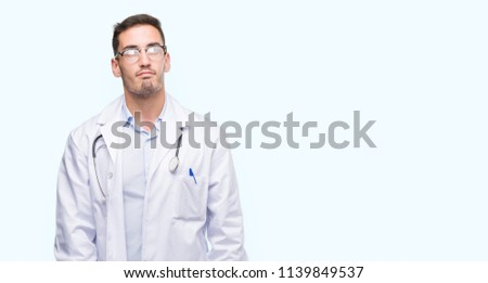 Handsome young doctor man smiling looking side and staring away thinking. #1139849537