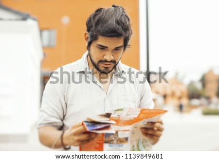 Attractive pensive brunette latin man looking at the map. Man is on foreground and focus, background is blurred. #1139849681