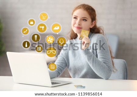 Young woman with credit card using laptop for online shopping at home #1139856014