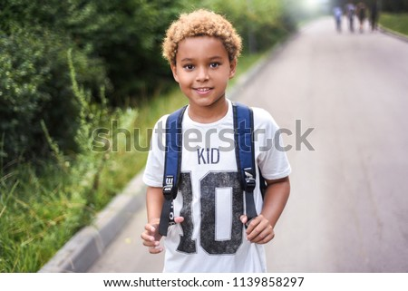 Portrait of the cute african american boy who is going to school with his school  backpack. Student mixed boy on his way to the school. Study for children. Road. Shooting on the july 2018.  Royalty-Free Stock Photo #1139858297