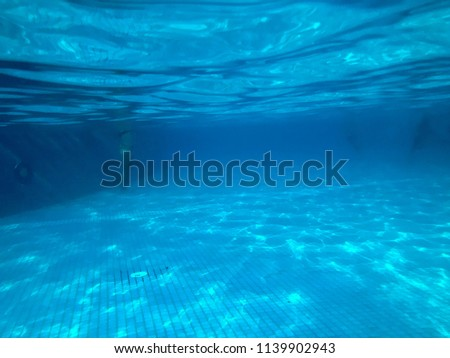 View swimming pool with ceramic tiles under blue water, underwater view of people in the pool in a tropical seaside resort, rest. #1139902943