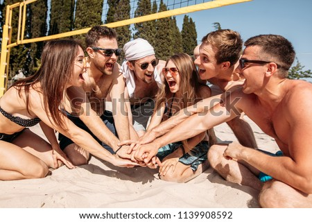 Give high five. Group of fit excited caucasian people talking in a circle, sitting on sand after volleyball game won. discussing goal, achieving team results. Teamwork, vacation, active life benefit #1139908592