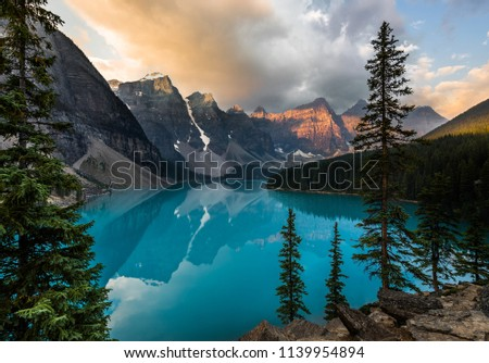 Sunrise with turquoise waters of the Moraine lake with sin lit rocky mountains in Banff National Park of Canada in Valley of the ten peaks. #1139954894