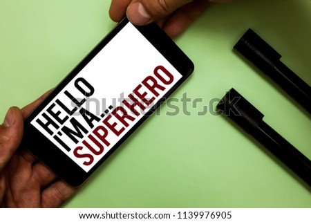 Text sign showing Hello I am A ... Superhero. Conceptual photo Special powers Cartoon character Customs strenght Man's hand hold iPhone with black and red words near two black marker.