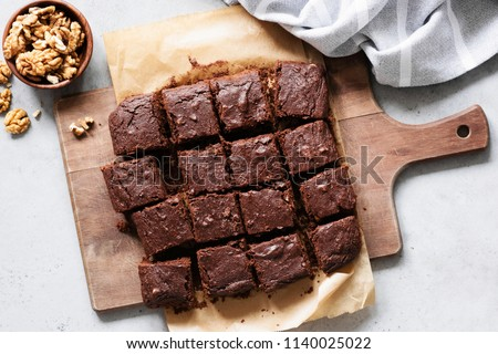 Chocolate brownie squares with walnuts on cutting board, top view, horizontal composition. Flat lay food #1140025022