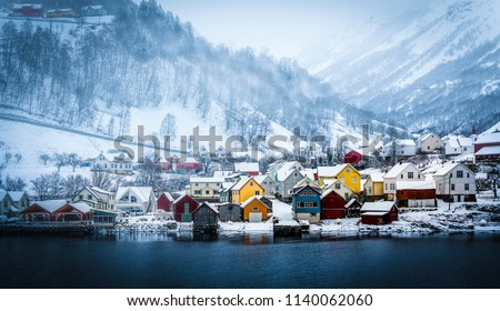 wooden houses on the banks of the Norwegian fjord, beautiful mountain landscape in winter #1140062060