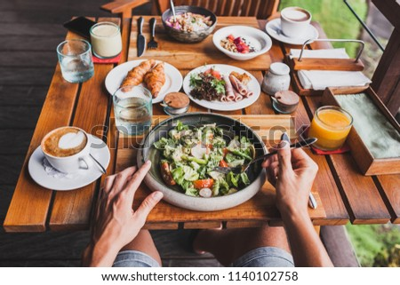 View from above on table with fresh breakfast. Man hands holding fork and knife #1140102758