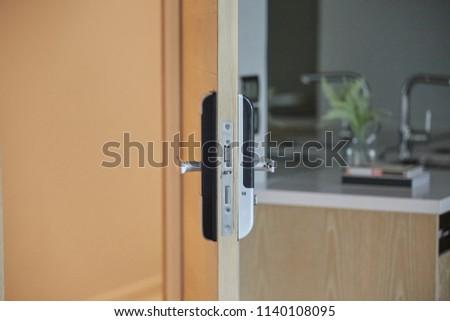 Digital door handle . Wooden door with knob door half opened in front of blur kitchen counter table. Close up, Selective focus. #1140108095
