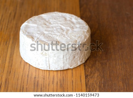 Camembert cheese round on oak wooden table close up #1140159473