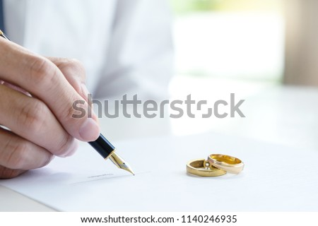 Hand man woman on paper with marry ring on paper to sign marriage or divorce #1140246935