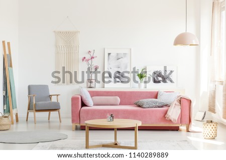 Patterned armchair next to pink sofa in apartment interior with posters and wooden table. Real photo #1140289889