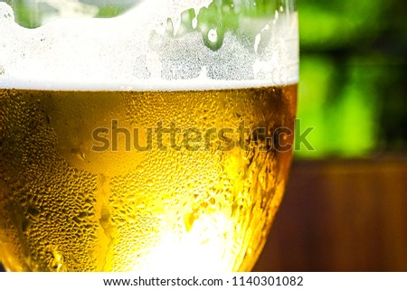 Refreshing Apple cider with ice cubes on a wooden table. Cider in the glass. Summer outdoor cafe. #1140301082