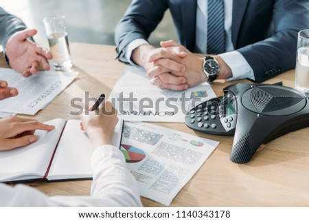 cropped shot of business people having conversation with documents and speakerphone on table at modern office #1140343178