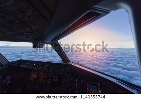 Sky view from airplane inside cockpit when airplane fly over the cloud. Seen in evening twilight. Royalty-Free Stock Photo #1140353744