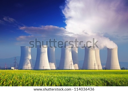 Nuclear power plant with yellow field and big blue clouds Royalty-Free Stock Photo #114036436