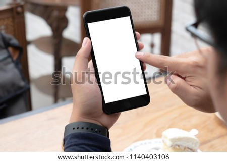 close-up on hand holding phone showing white screen on desk at coffee shop. #1140403106