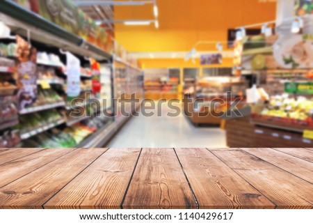 Empty wood table top on shelf in supermarket blurred background Royalty-Free Stock Photo #1140429617