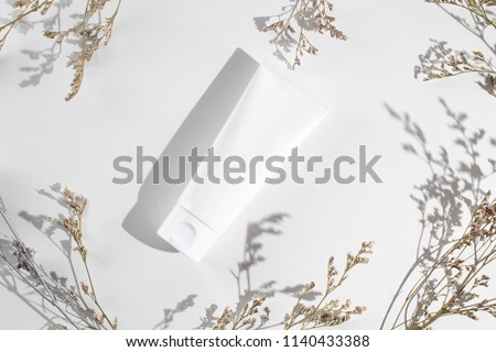white beauty cream lotion spf sunscreen cosmetic spa tube packaging product mockup with cassia flower leaf herb in sun morning daylight with summer concept, top view of facial skin care, healthcare  #1140433388