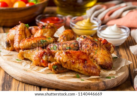 Grilled chicken wings with ketchup and mustard sauces on a wooden board. Traditional baked bbq buffalo Royalty-Free Stock Photo #1140446669