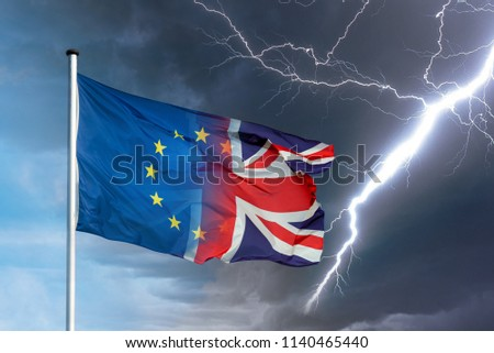 Merging european and british flag with lightning bolt in front of dark clouds in sky as a symbol for the Brexit #1140465440