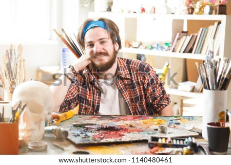 Portrait of happy bearded caucasian male artist in blue bandana holding brush and smiling in his sunny studio #1140480461