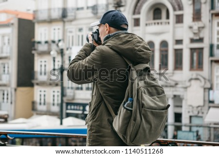 A professional travel photographer or tourist photographs a beautiful urban landscape in Porto in Portugal. Professional occupation or hobby #1140511268