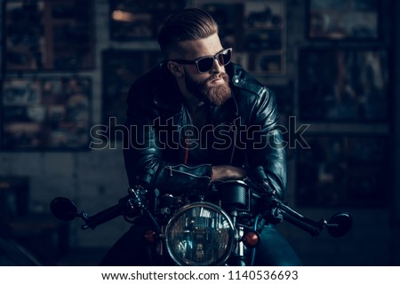 Young Bearded Biker Sitting on Motorcycle in Garage. Indoor Garage. Young Mechanic in Garage. Parts of Motorcycle. Man in Checkered Shirt. Man on Vintage Bike. Biker Lifestyle Concept. Royalty-Free Stock Photo #1140536693