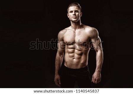 Muscular model young man on dark background. Fashion portrait of strong brutal guy with trendy hairstyle. Sexy naked torso, six pack abs. Male flexing his muscles. Sport workout bodybuilding concept. #1140545837