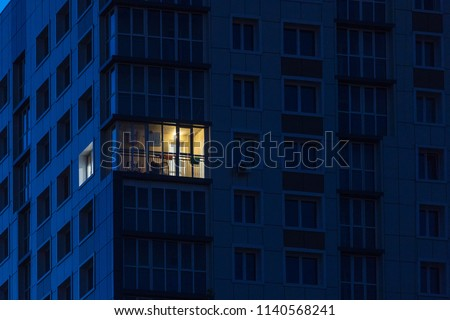 the light burns in one window of the multitude in a multi-storey residential building  #1140568241