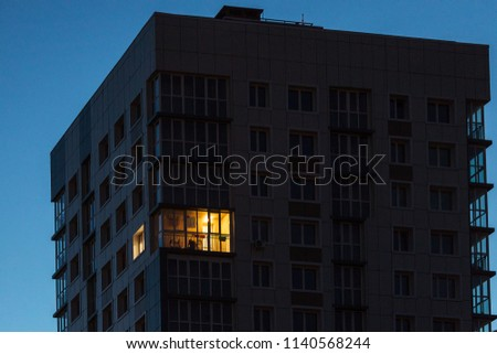the light burns in one window of the multitude in a multi-storey residential building  #1140568244