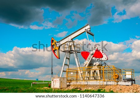 Oil pump tower in the field with green grass with blue cloudy sky. #1140647336