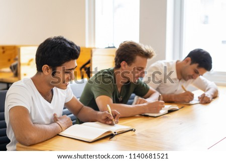 International company employees taking refresh training. Multiethnic group of three students writing notes during class. Career course concept #1140681521