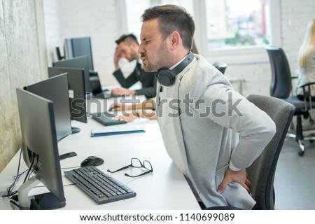 Businessman suffering from backache in office #1140699089